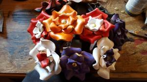 Added in 2015.  Molded leather roses, hand painted.  Can be worn as a hairclip, on a scarf, jacket, hat.  Also made attached to a leather band to worn as a bracelet or wrapped around a scarf.